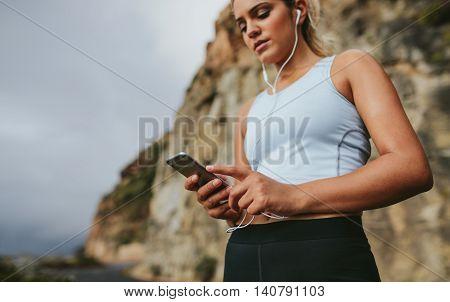 Female Runner Taking A Break And Listening To Music