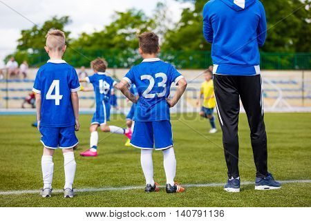 Young soccer players with football coach. Soccer tournament for youth school sports teams.