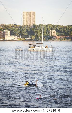 NEW YORK -?? JUL 24 2016: Lifeguard on a surfboard patrol the route as athletes compete in the NYC Triathlon Race in New York. The swim portion is 1.5 kilometers in the Hudson River at Riverside Park.