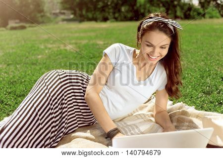 Positivity in mind. Delighted overjoyed smiling woman using laptop and sitting on the grass while resting