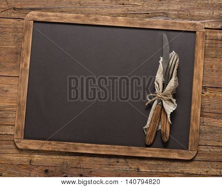 Top view of vintage fork and spoon tied with string on linen napkinon a blackboard on a old wooden table with copy space.