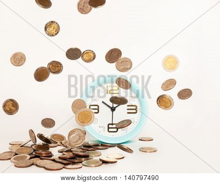 Close up of alarm clock stacking silver coins falling on white background