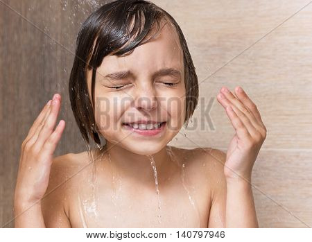 Smiling beautiful little girl bathing under a shower - washing head, in the bathroom at home
