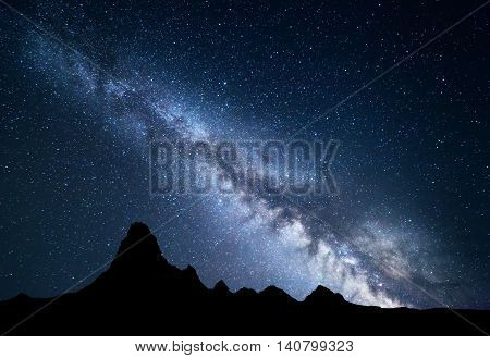 Night landscape with amazing Milky Way and mountain peak. Starry sky with high rocks at summer. Beautiful Galaxy. Universe. Space background. Travel