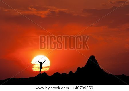 Sunset landscape with silhouette of a standing happy woman and raised-up arms. Girl on the mountain peak against the sun and colorful sky in summer. Travel background