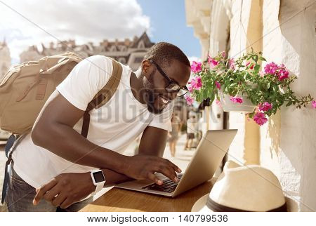 Lets check. Cheerful delighted smiling man leaning on the table and using laptop while standing outside the cafe