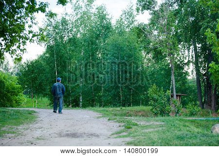 Homeless man walking in park. outdoor walk