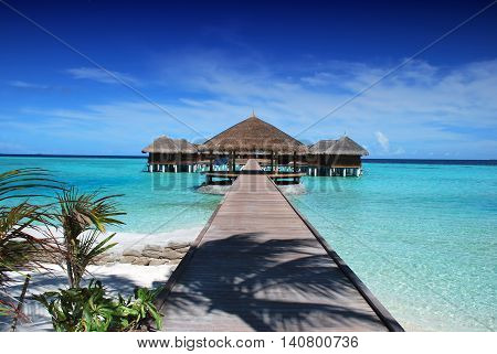 Bungalows on water and wooden jetty with turquiose water on Maldives