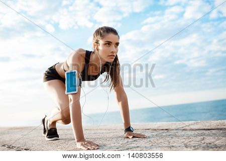 Young beautiful brunette sportive girl preparing to run over seaside. Copy space.