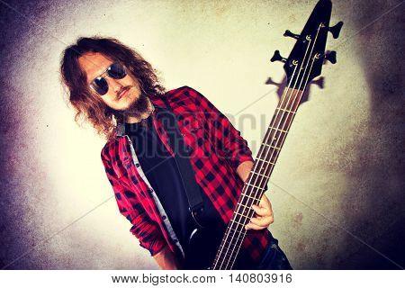 Guitarist playing bass guitar. Retro instagram vintage grunge picture.