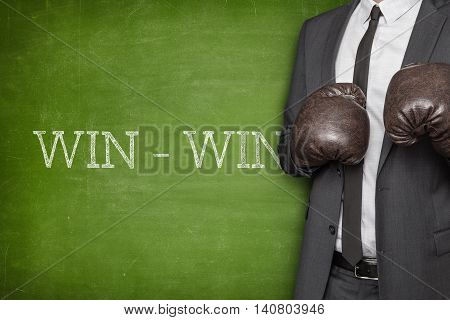 Win - win on blackboard with businessman wearing boxing gloves