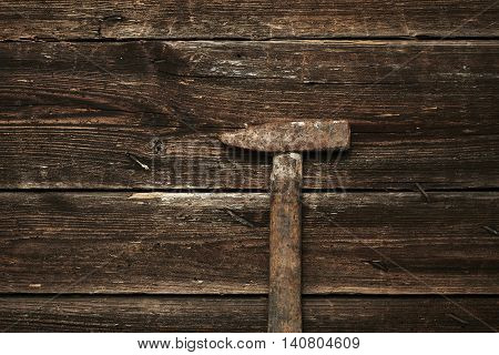 Old steel hammer with wooden handle on the wooden boards background