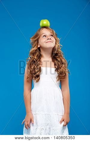 Young pretty girl holding green apple  on head, smiling over blue background.