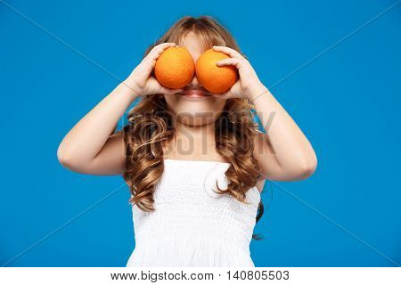 Young pretty girl hiding eyes wit oranges, smiling over blue background. Copy space.