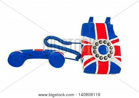 Union Jack telephone with pattern of British flag telephone with the receiver off the hook laying in front of the phone isolated on the white background. Selective focus at the receiver