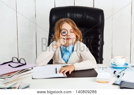 Young beautiful girl sitting at working place, looking to camera through magnifier in office.