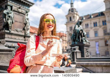 Young female traveler eating sausage on the central square in Graz. Austrian traditional street food