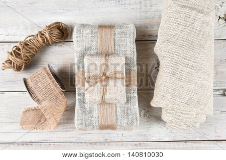 Top view of the tools for wrapping Christmas presents with burlap fabric and ribbon with twine on a white wood surface.
