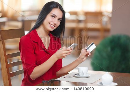 Business woman shopping online. Business woman pays for a purchase with credit card. Beautiful girl in red shirt makes a purchase on the Internet. Buy online. Shopping online