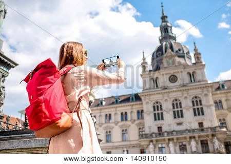 Young woman photographing with phone town hall building in Graz old town. Traveling in Austria