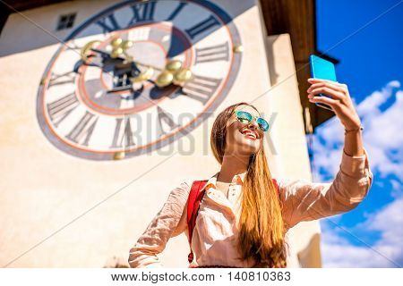 Young female traveler making selfie photo with smart phone on the old clock tower background in Graz town. Traveling in Austria