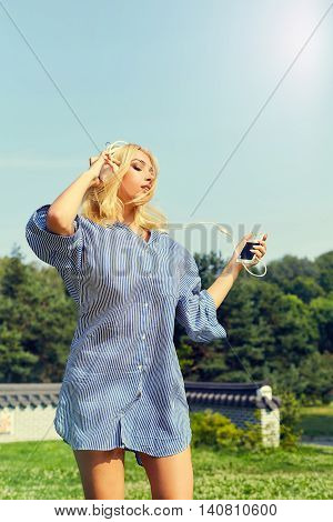 Woman dancing while listening to music in park. Young woman listening and dancing to music with earphones, having fun and relaxing. Woman dance and enjoys music on green grass.