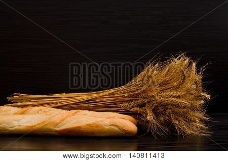 Sheaf and white loaves on a black background with space for text