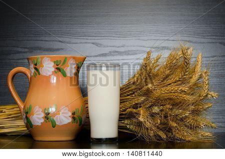 Jug glass of milk and a sheaf on a dark background