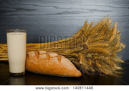 A glass of milk whole wheat bread and a sheaf on a dark background