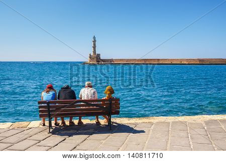 Chania, Crete - 23 Maj, 2016: People Sitting On The Bench In The Old Harbor Of Chania On Crete, Gree