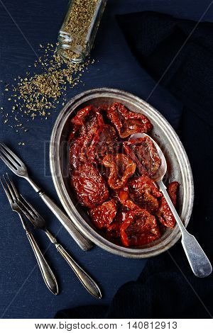 Sundried Tomatoes in the pot on the wooden background