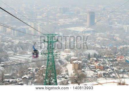 ALMATY, KAZAKHSTAN - MARCH, 10 2014: funicular with tourists and view of the foggy city of Almaty Kazakhstan