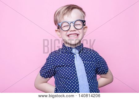 Stylish boy in shirt and glasses with big smile. School. Preschool. Fashion. Studio portrait over pink background