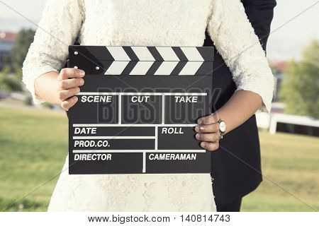 Happy beautiful bride and groom, woman holds clapper board, cinema board