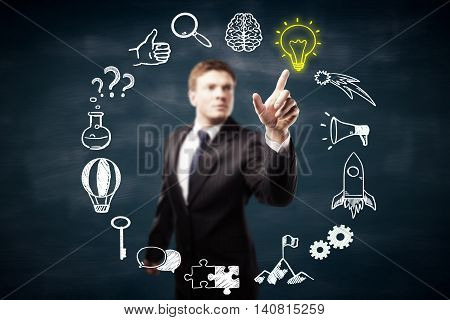 Blurry businessperson pointing at circular business icons sketch on blackboard background. Success and idea concept