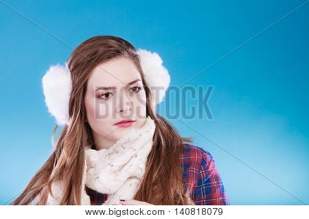 Young woman wearing fluffy white earmuff. Teenage in cold time.