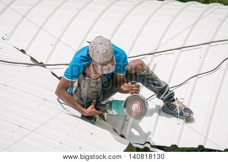 Worker with saw on the roof.