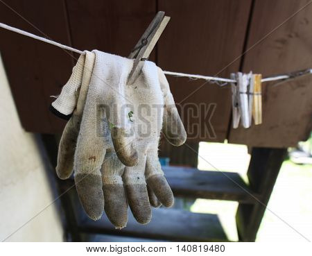 Dirty work gloves on a clothesline outdoors