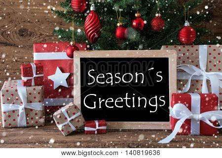 Colorful Christmas Card For Seasons Greetings. Christmas Tree With Balls And Snowflakes. Gifts Or Presents In The Front Of Wooden Background. Chalkboard With English Text Seasons Greetings