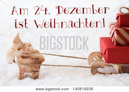 Moose Is Drawing A Sled With Red Gifts Or Presents In Snow. Christmas Card For Seasons Greetings. German Text Am 24. Dezember Ist Weihnachten Means Christmas