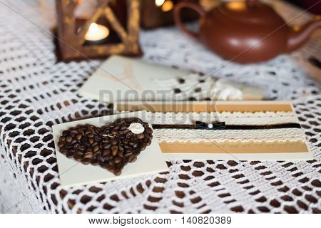 postcard with coffee beans in the shape of a heart is on the white tablecloth