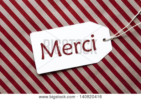 One Label On A Red And Brown Striped Wrapping Paper. Textured Background. Tag With Ribbon. French Text Merci Means Thank You