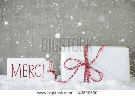 One Christmas Present On Snow. Cement Wall As Background With Snowflakes. Modern And Urban Style. Card For Birthday Or Seasons Greetings. Label With French Text Merci Means Thank You