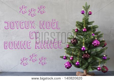 Christmas Tree With Purple Christmas Tree Balls. Gray Cement Or Concrete Wall For Urban, Modern Industrial Style. French Text Joyeux Noel Et Bonne Anne Means Merry Christmas And Happy New Year