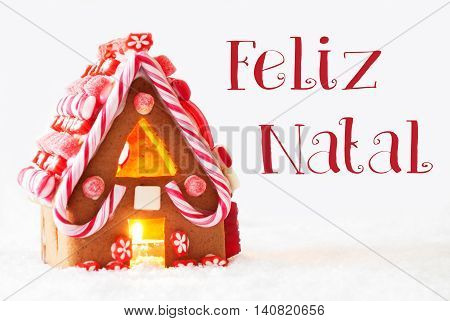 Gingerbread House In Snowy Scenery As Christmas Decoration With White Background. Candlelight For Romantic Atmosphere. Portuguese Text Feliz Natal Means Merry Christmas
