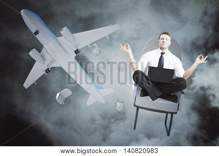 Meditating man with laptop falling out of airplane on night sky background