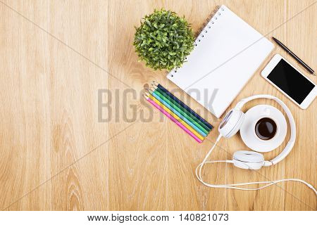 Top view of wooden desktop with blank spiral notepad coffee cup headphones blank smartphone colorful pencils and decorative plant. Mock up