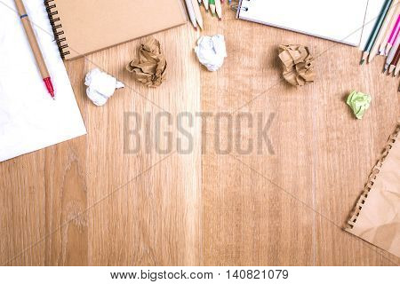 Top view of messy wooden desktop with variety of stationery items and crumpled paper balls. Mock up