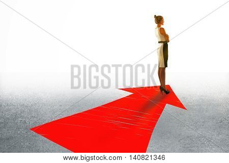 Success concept with businesswoman standing on large red arrow