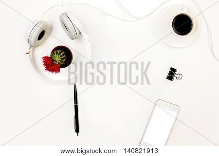 Top view of white desktop with blank smartphone headphones small cactus pen peg and coffee cup. Mock up